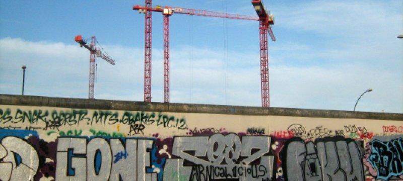 Baukräne an einem Rest der Berliner Mauer