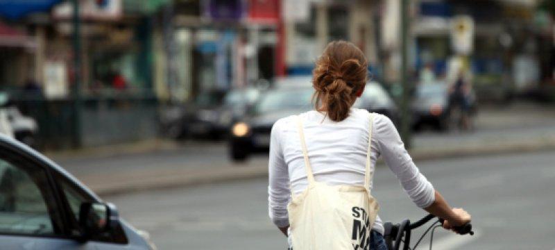 Junge Frau auf Fahrrad im Straßenverkehr