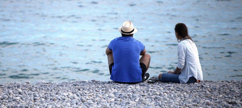 Mann und Frau sitzen am Strand